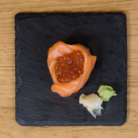 composition of fish food, salmon fillets mounted in the shape of a cup, stuffed with caviar, plate served on a slab of slate, garnished with ginger and wasabi, squared image