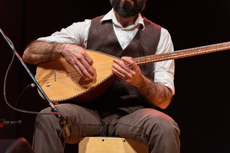 Good-looking man with a thick black beard, hands details of a musician playing a typical stringed instrument on stage, the tembur or saz
