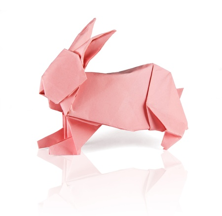 pink origami rabbit on the white reflecting background photo