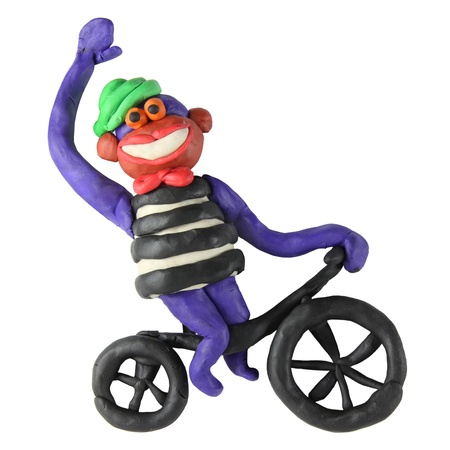 Plasticine monkey on the bicycle on a white background