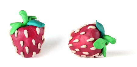red plasticine strawberries on the white background