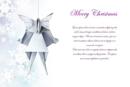 Christmas silver origami angel on a snowflakes background photo