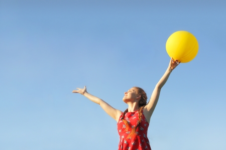 Girl in red dress whith sun yellow baloon on a sky background Stock Photo - 19754095