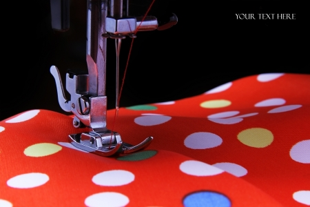 Sewing machine in the studio scribbling a red fabric with polka dots Stock Photo - 19686999