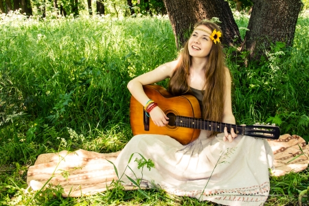 Hippie ethnic smiling girl singer with guitar in the forest photo