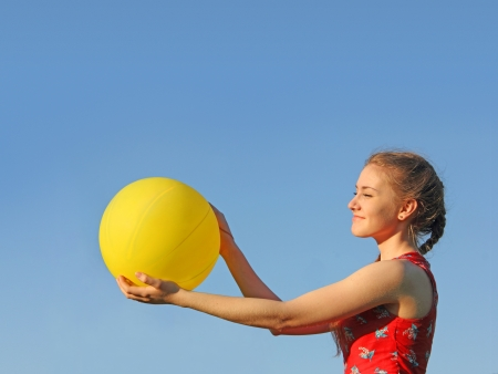 Girl with yellow sun baloon in hands on blue sky background Stock Photo - 19754094