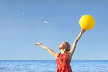 Girl in red dress with sun yellow baloon on the sky and sea background whith seagulls Stock Photo - 19754096