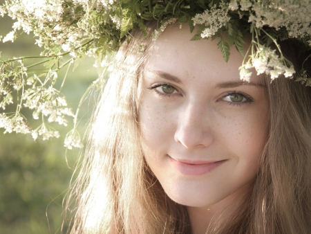 Girl with freckles in flower wreath in the forest