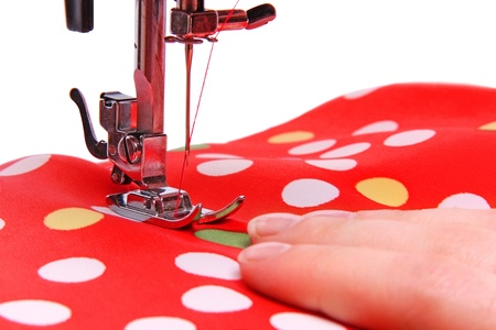 Sewing machine in the studio scribbling a red fabric with polka dots on a white background Stock Photo - 19687004