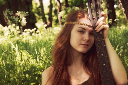 Hippie ethnic smiling girl singer with guitar in the forest Stock Photo - 19856562