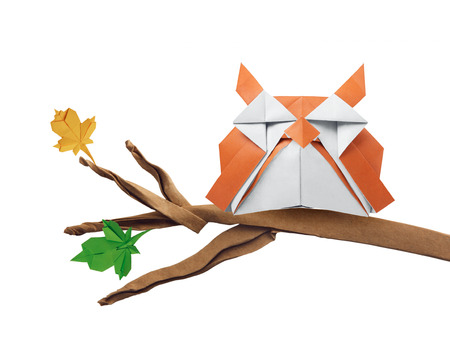 Origami art owl bird on a branch isolated on white