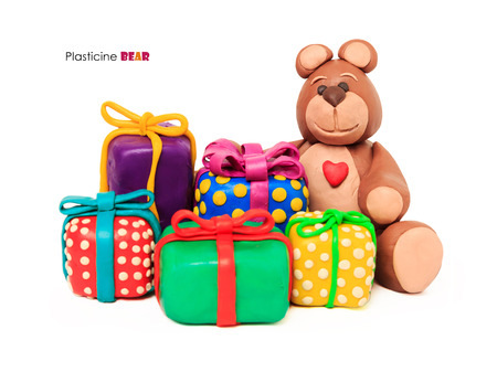 Plasticine chocolate happy bear whith gift holiday boxes on a white background