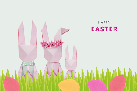 asian bunny: Easter origami rabbits family in grass with eggs on a green background Stock Photo