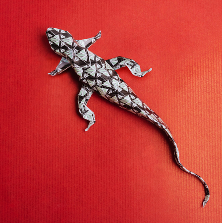 Origami paper art wild lizard on a red paper background Stock Photo