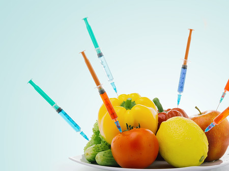 modification: Toxic gmo vegetables modification syringe isolated on a blue background