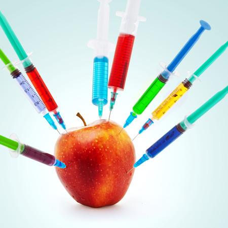 Toxic gmo apple fruit modification syringe isolated on a blue background