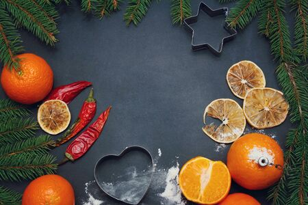 Spices flour orange food pine tree branchon a black board winter christmas background