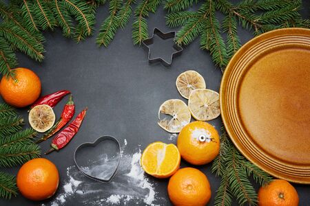 Spices flour orange pine tree branch and empty plate on a black board winter christmas background