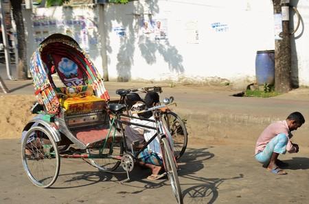 rikscha: DHAKA, BANGLADESH - NOVEMBER 2: Driver of a rickshaw squats on the street, Rickshaw empty on November 2, 2014 in Dhaka, Bangladesh
