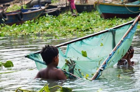 2 november: DHAKA, BANGLADESH - NOVEMBER 2: Bangladeshi kids are in the Buriganga river with a fishing net on November 2, 2014 in Dhaka, Bangladesh