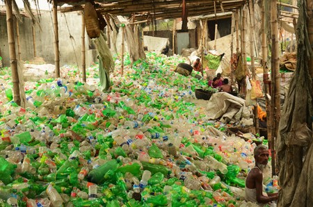 recycle area: DHAKA, BANGLADESH - NOV 9: A mountain of green and white plastic bottles, stacked for recycling on November 9, 2014 in Dhaka, Bangladesh