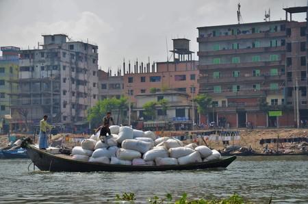 2 november: DHAKA, BANGLADESH - NOVEMBER 2: A boat loaded with white bags on a river on November 2, 2014 in Dhaka, Bangladesh