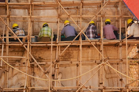 restoring: Bagan, Myanmar - CIRCA FEBRUARY 2015: Builders are sitting on a scaffolding wearing yellow helmets and restoring an ancient temple circa February 2015 in Bagan, Myanmar