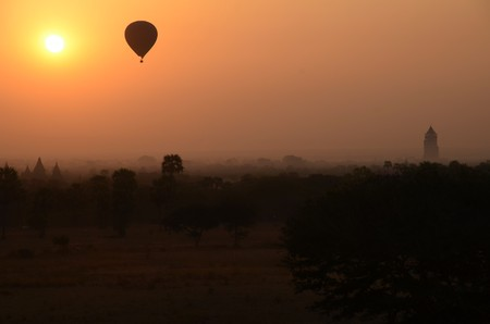 longshot: A hot-air balloon is flying in an orange, yellow sky, some temples are visible in the background, longshot