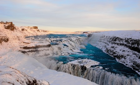 plan éloigné: A long shot of the Gullfoss waterfall with turquoise water in Iceland during sunset in winter
