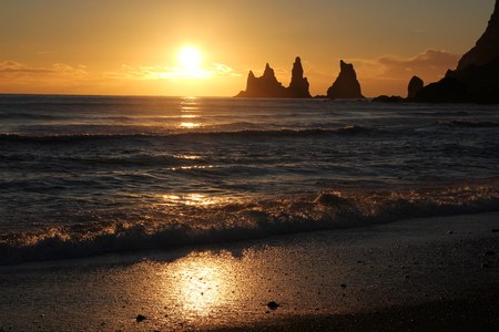 longshot: Golden sky behind the stones Reynisdrangar, longshot from the black beach in Vk