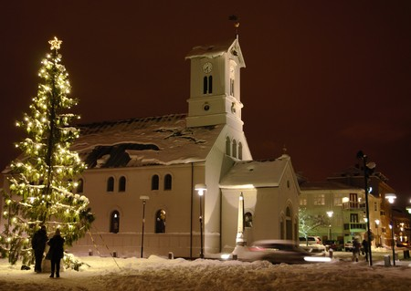 plan éloigné: Long shot of a church in Reykjavik, in front a lit up Christmas tree