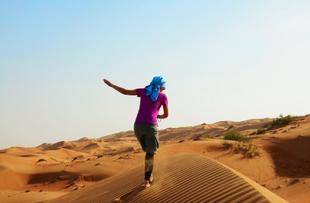 head scarf: A woman with a head scarf is running up blue a sand dune Stock Photo