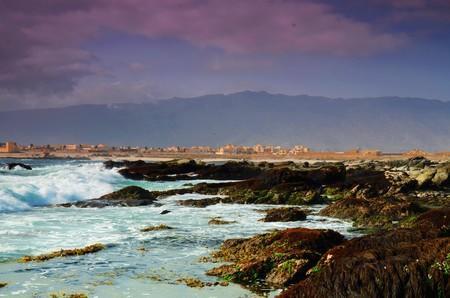 plan �loign�: Long shot de l'oc�an, les vagues sauvages et vert, brownstones, la ville Sur Oman en arri�re-plan Banque d'images