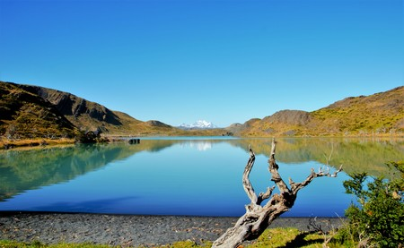 onto: Pudeto, Torres del Paine NATIONAL PARK, CHILE - FEBRUARY 5, 2016: View onto a lake with a snow covered mountain in the background, brown hills Stock Photo