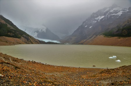 Laguna Torre Trek in El Chalta  n, greywater with icebergs in it, very cloudy day, snow covered mountains in the background and a glacier Stock Photo