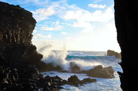Waves breaking at the cliffs in front of the Ana Kai Tangata Cave close to Hanga Roa in Rapa Nui, Easter Island in Chile, South America Stock Photo