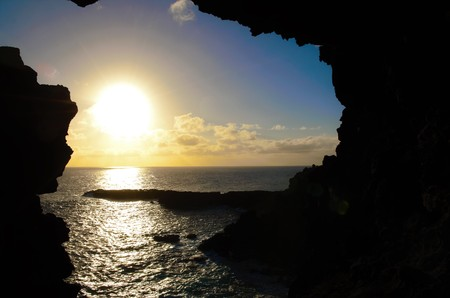 View onto the ocean during sunset through one of the windows at the Ana Kakenga Cave or two windows cave in Easter Island, Rapa Nui, Chile, South America Stock Photo