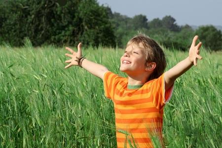 oneness: Felice bambino sorridente braccia sollevate nella gioia  Archivio Fotografico