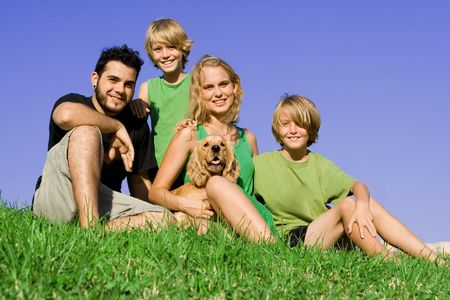 happy smiling young family outdoors with pet dog photo