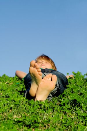 barefooted: happy child relaxing in grass outdoors