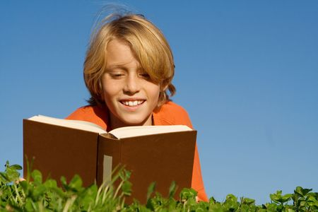 happy child reading book outdoors