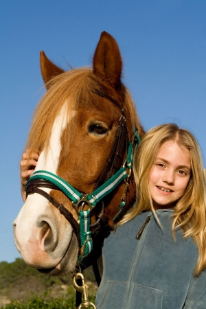 horse harness: happy child stroking pet horse Stock Photo