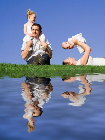 lying in grass: Familia feliz jugando al aire libre