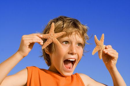 goofing: happy child on summer vacation showing starfish