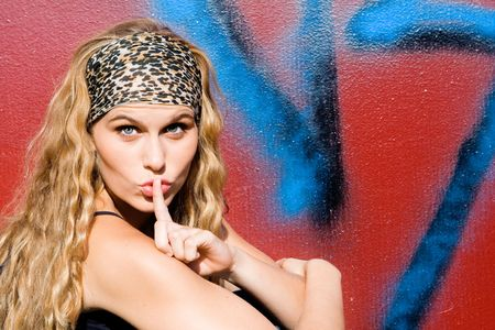 pretty young woman with fingers on lips photo