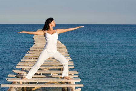 woman doing tai chi on beach Stock Photo