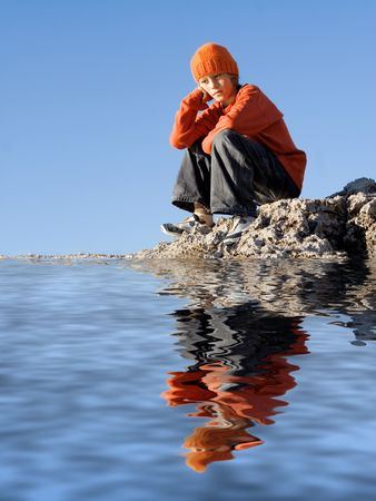 friendless: bored lonely child sitting by sea