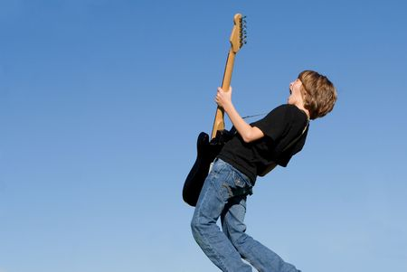 tweens: Happy child singing and playing guitar Stock Photo