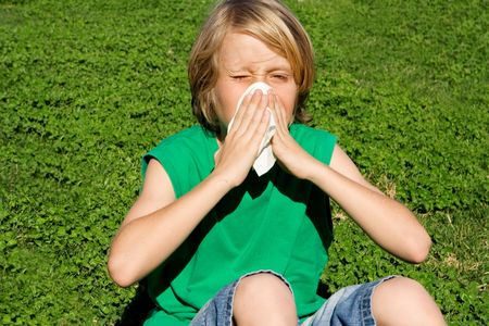 Child with cold or allergy blowing nose photo