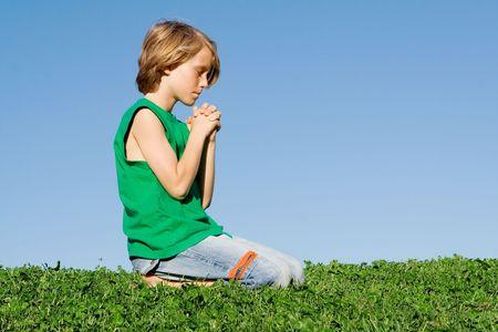 Christian child kneeling praying outdoors photo